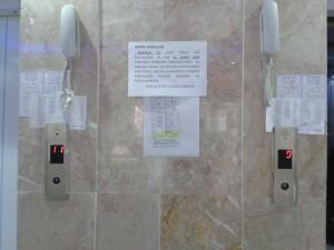 """Resim: Çelişkiler tablosu. Çift asansörlü, asansör telefonu ve mermer döşeli lüks sitede, duvarlara yapıştırılmış, metallere iliştirilmiş duyuru ve """"para toplama"""" kağıt parçaları."""